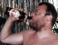 Nackter Mann nuckelt an Bierflasche